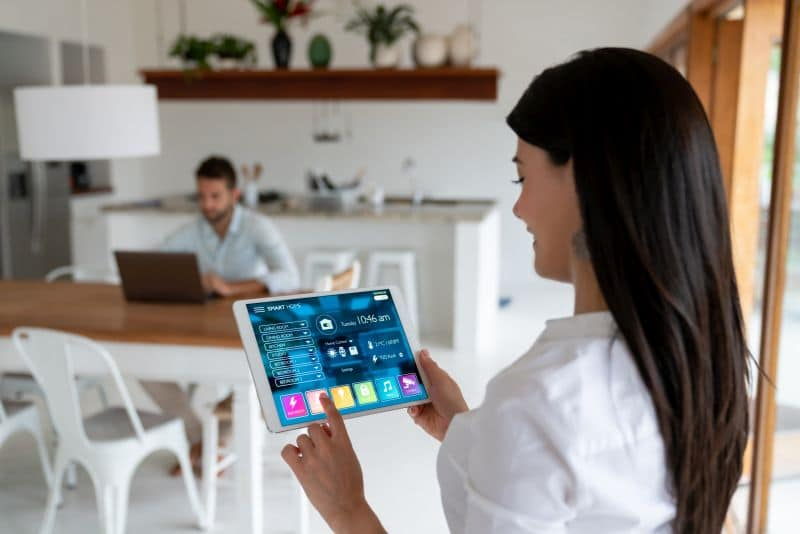 Woman setting up the intelligent home system on her tablet computer