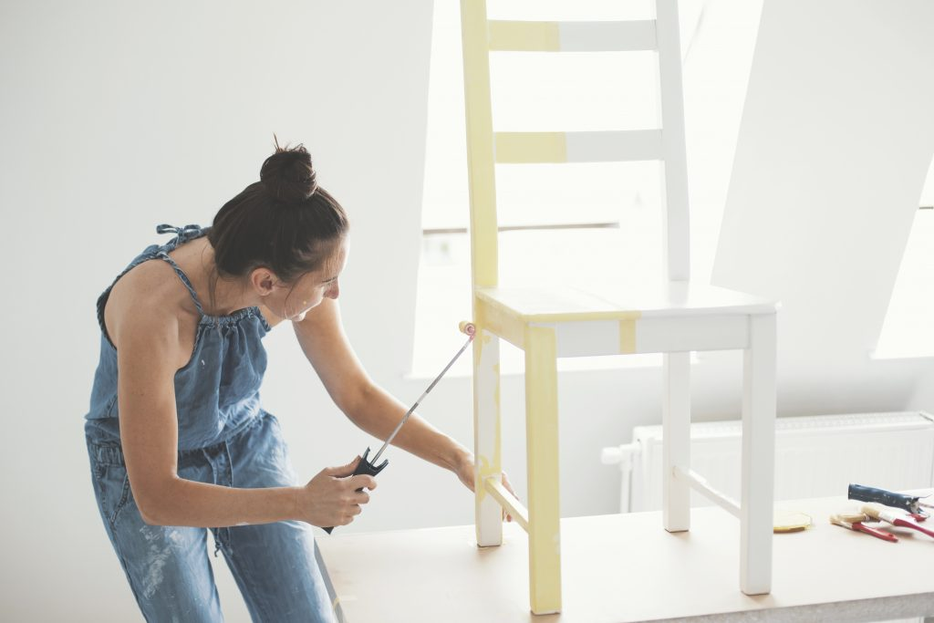 Mid adult woman painting chair